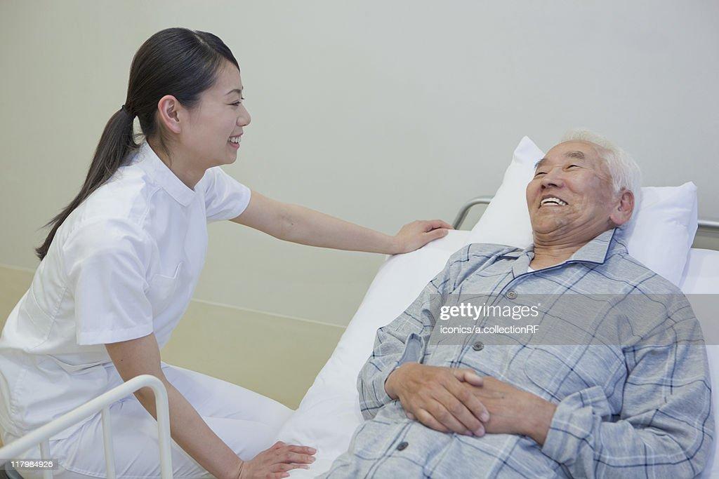 Senior man lying on bed talking to nurse, Kanagawa Prefecture, Honshu, Japan : Stock Photo
