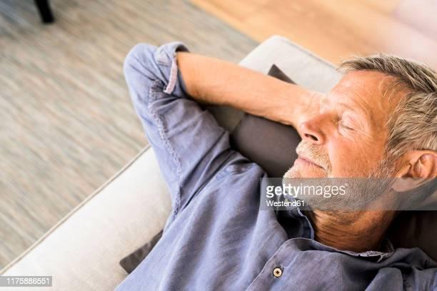 senior man lying on couch at home taking a nap - hände hinter dem kopf stock-fotos und bilder