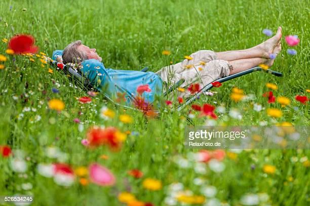 Senior man lying on deck chair in garden