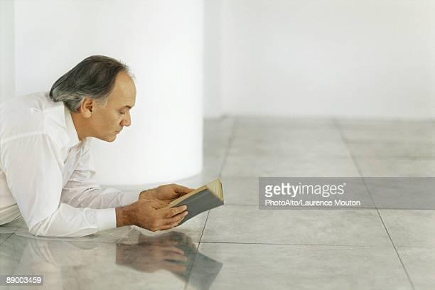 Senior man lying on tiled floor reading book