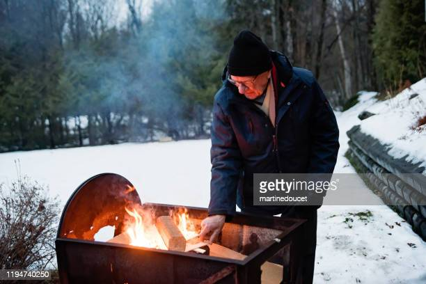 "senior man making a fire outdoors in winter - ""martine doucet"" or martinedoucet stock pictures, royalty-free photos & images"