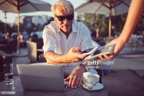 Senior man maken contactloze betalingen in café