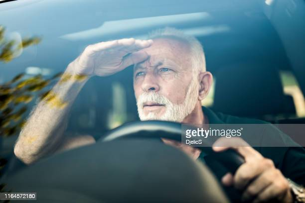 senior man making effort to see the road while driving his car. - eyesight stock pictures, royalty-free photos & images