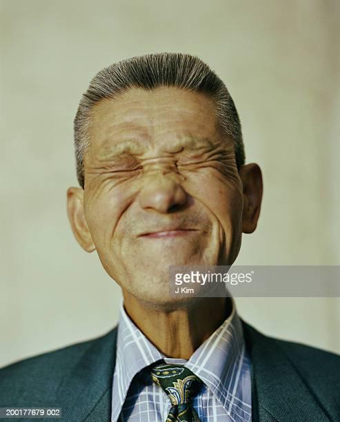 Senior man making face, eyes closed