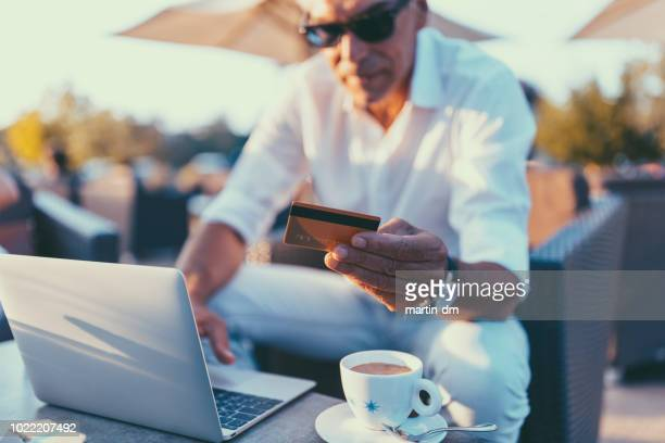 senior man making online shopping - making a reservation stock photos and pictures
