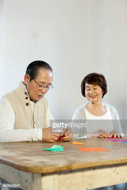 Senior man making origami next to senior woman at table