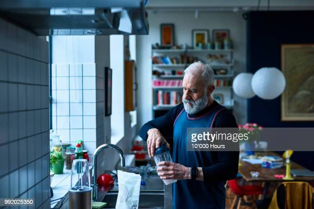 senior man making protein shake before exercising - protein drink stock pictures, royalty-free photos & images
