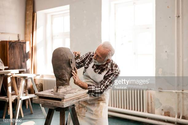 senior man making statue of clay shaping a face with work tool - pottery stock pictures, royalty-free photos & images