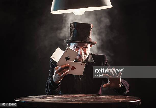 senior man making trick with playing cards - goochelaar stockfoto's en -beelden