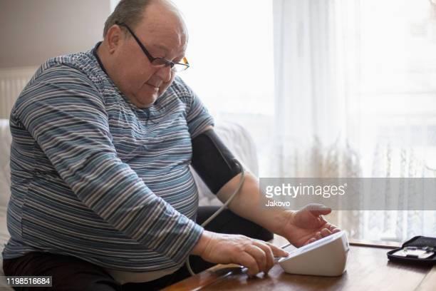 自宅で血圧を測定するシニア男性 - 状態 ストックフォトと画像