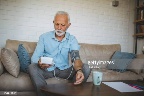 senior man measuring his blood pressure - hypochondria stock photos and pictures