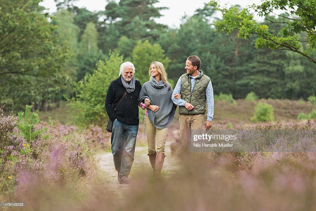 Senior man, mid adult man and woman walking through forest : Stockfoto