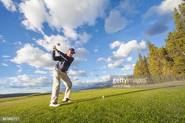 senior man mid swing at a golf tee box - ティーグラウンド ストックフォトと画像