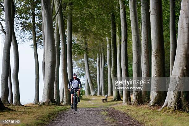 Senior Man Mountain Biking Along a Forest Trail