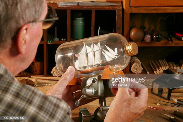 Senior man mounting ship in bottle on display stand, rear view