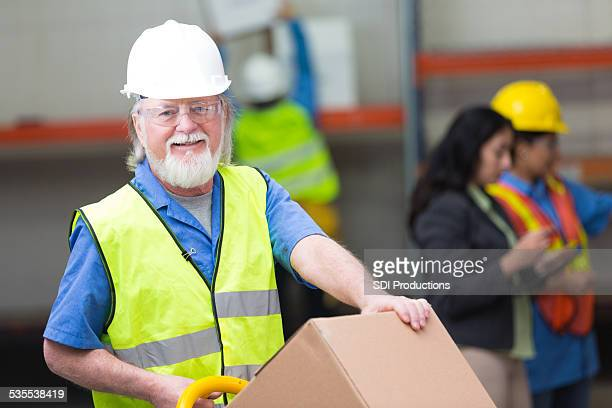 Senior man moving boxes in shipping and distribution warehouse