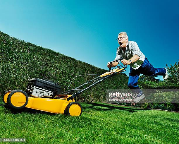 Senior man mowing lawn, jumping, mouth open, low angle view