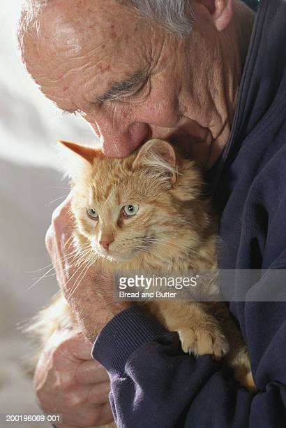 senior man nuzzling pet cat - hairy old man stock pictures, royalty-free photos & images
