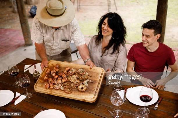 homme aîné offrant le barbecue à la famille à la maison de campagne - churrasco - argentine photos et images de collection