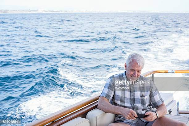 senior man on a boat trip looking at cell phone - alleen seniore mannen stockfoto's en -beelden