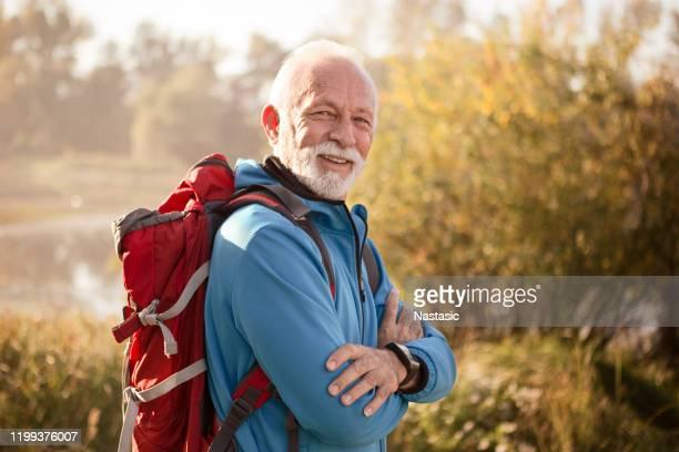 senior man op een voetpad wandelen poseren met glimlach - alleen één man stockfoto's en -beelden