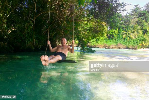 senior man on a swing over a tropical river in jamaica - jamaica stock pictures, royalty-free photos & images