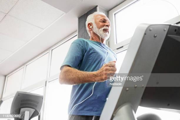 homem sênior em um funcionamento do proibir da escada rolante - 65 69 anos - fotografias e filmes do acervo