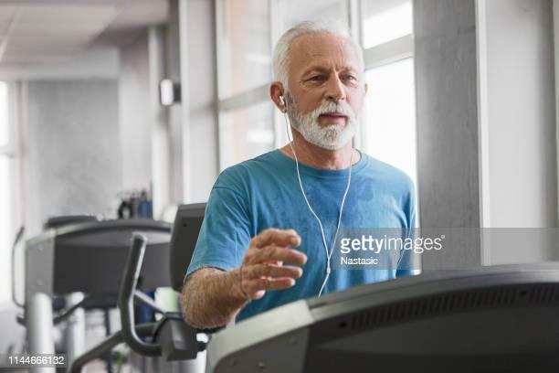 homem sênior em uma escada rolante no centro de aptidão - 65 69 anos - fotografias e filmes do acervo
