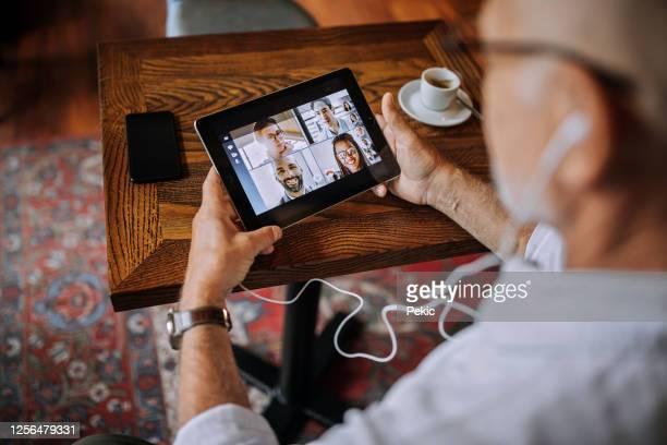 hogere mens op een videovraag in een koffie - alleen seniore mannen stockfoto's en -beelden