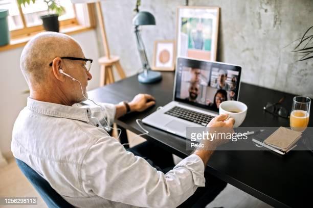 hogere mens op een videoconferentievraag in zijn huisbureau - alleen seniore mannen stockfoto's en -beelden
