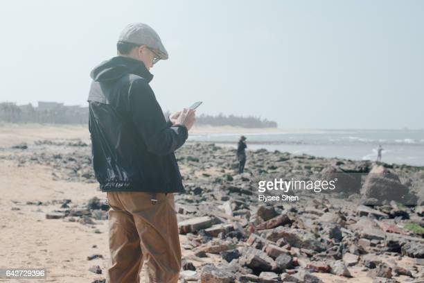 senior man on beach using smart phone - haikou stock pictures, royalty-free photos & images