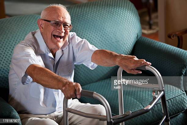 Senior man on couch with walker, laughing
