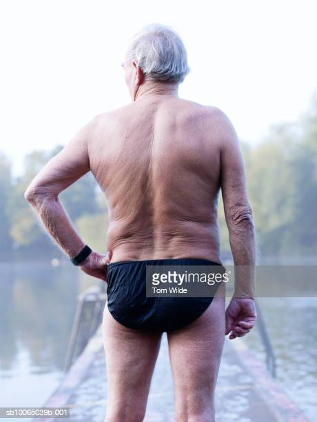 Senior man on diving board, rear view