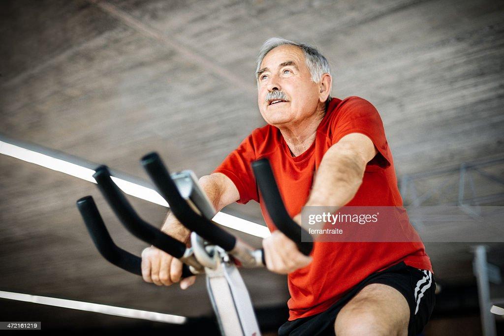Senior Man on exercising Bicycle : Stock Photo