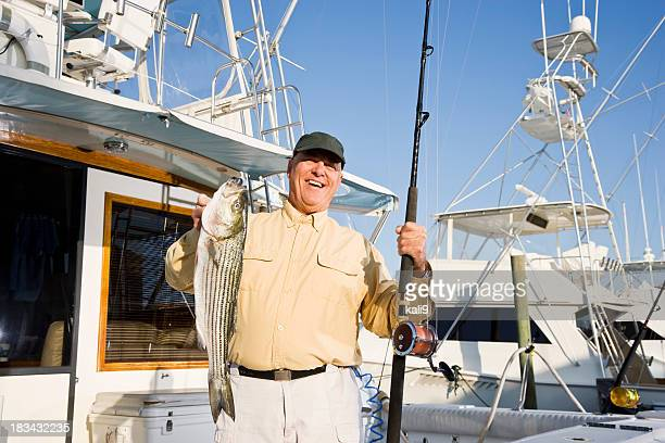 senior man on fishing boat in marina with fresh catch - big game fishing stock photos and pictures