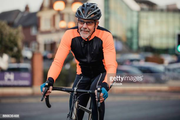 a senior man on his racing bike - cycling helmet stock photos and pictures