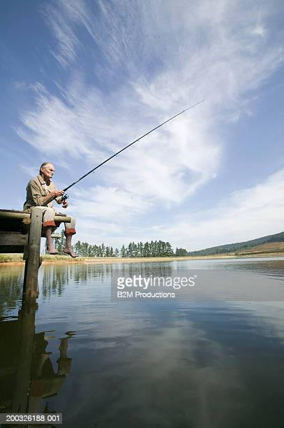 Senior man on jetty fishing in lake, low angle view