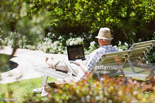senior man on lounge chair using laptop - feet up stock pictures, royalty-free photos & images