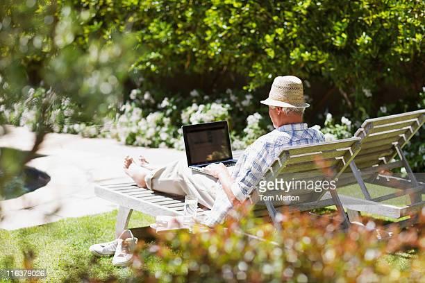 Alter Mann mit laptop auf der lounge-Sessel