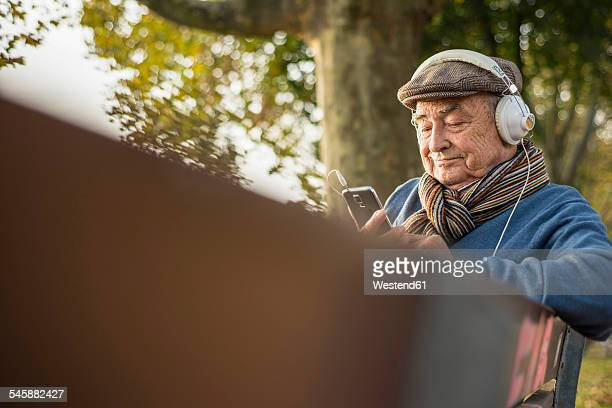 Senior man on park bench with cell phone and headphones