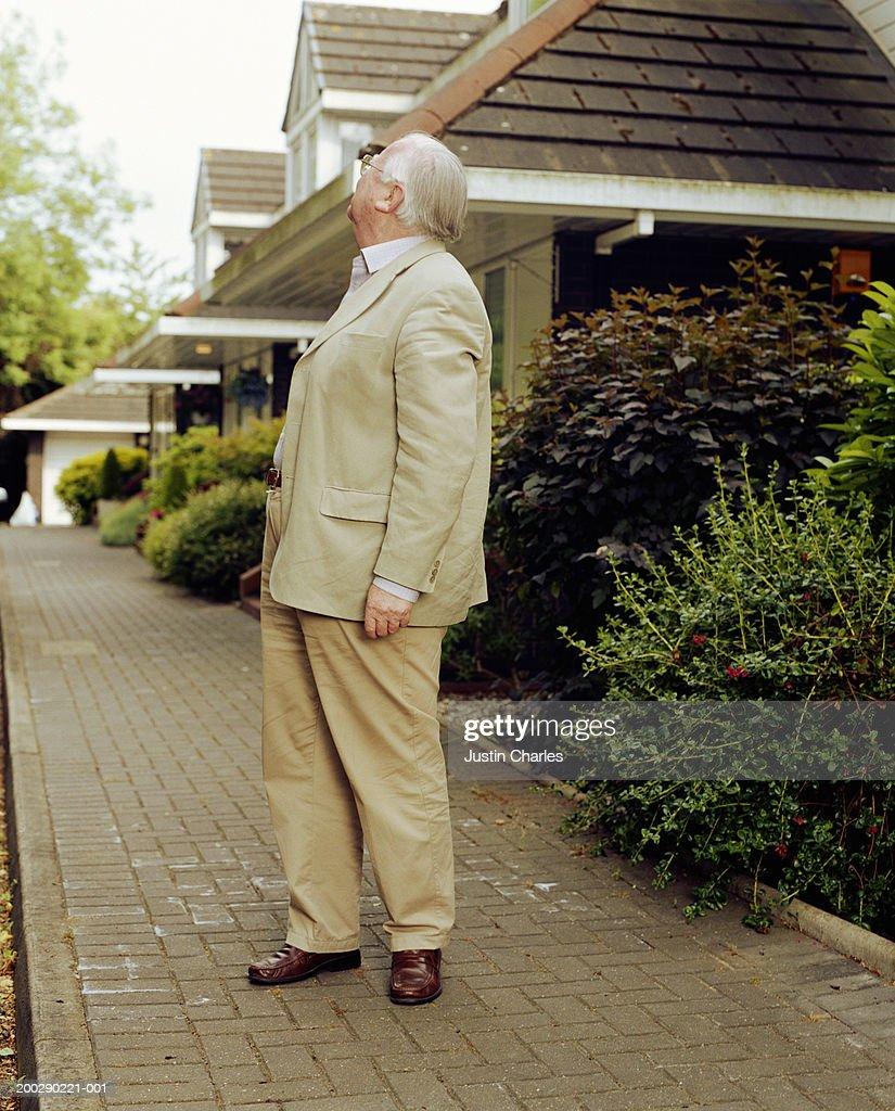 Senior man on pavement, looking away : Stock Photo