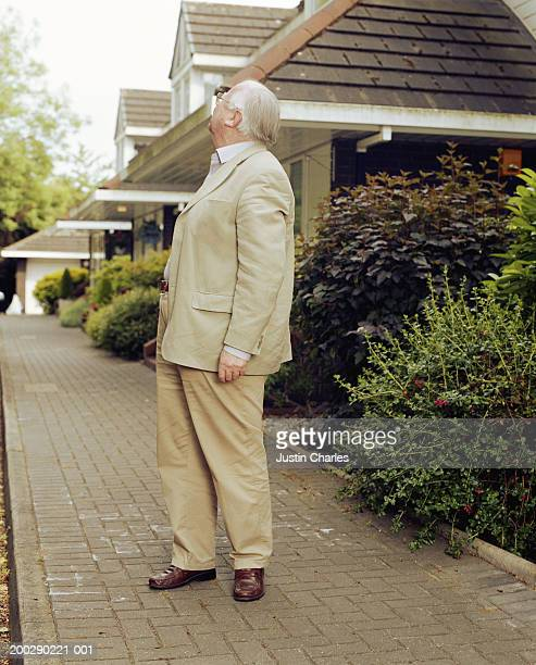 Senior man on pavement, looking away