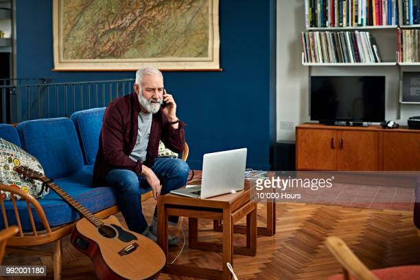 senior man on phone at home in retro living room - one man only stock pictures, royalty-free photos & images