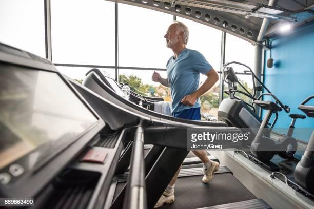 モダンなジムでマシンを実行している年配の男性