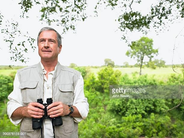 Senior man on safari holding binoculars, smiling