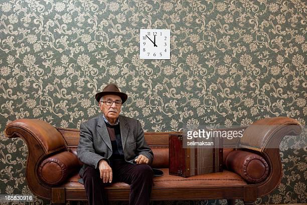 Senior hombre en el sofá con su maleta listo para salir de