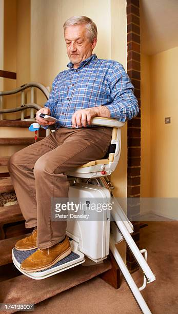 senior man on stair lift - fragility stock pictures, royalty-free photos & images