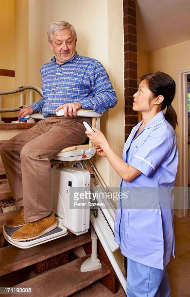 senior man on stair lift with nurse - elevador de escada imagens e fotografias de stock