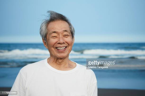 senior man on sunny beach - japanese old man stock pictures, royalty-free photos & images