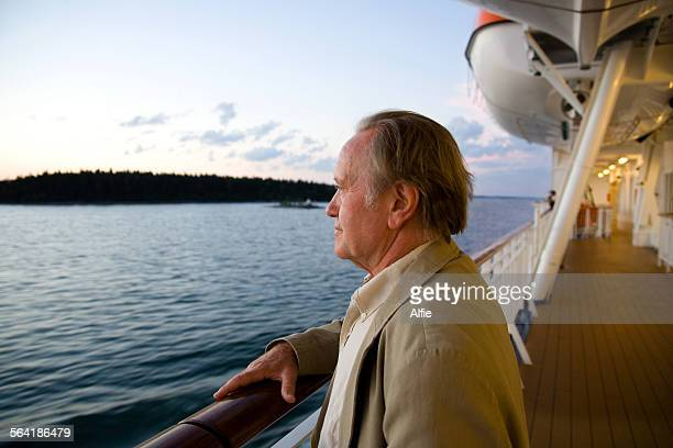 Senior man on the deck of a ship looking out to sea